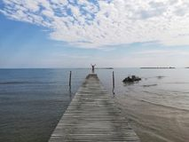 Man jumps on the pier. Between sky and sea Stock Photos