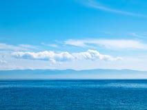 Sky, sea and mountainous island. Stock Photos