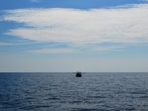 Fishing boat on the horizon of the sea royalty free stock image
