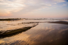 Sky and sea. Waves on the beach at the sunset Stock Photos