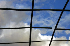 Sky seen through grid. A view of open, partly cloudy sky overhead as seen through a grid or skylight Royalty Free Stock Photo