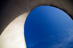 Sky shown through a curvy concrete structure . Hor Royalty Free Stock Photo