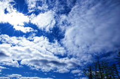 Sky. Small clouds of white color, the sun behind clouds with visible beams, against the background of the blue sk Royalty Free Stock Photo
