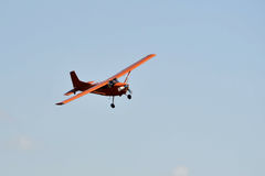 In the sky the small orange plane flies. Royalty Free Stock Photos