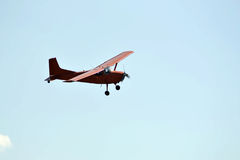 In the sky the small orange plane flies. Royalty Free Stock Photography