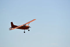 In the sky the small orange plane flies. Stock Images