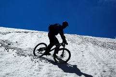 Sky, snow and mountain biker. Downhill from mountain pass Stock Photos
