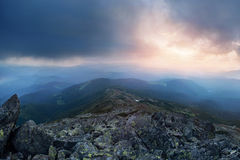 Sky before the storm in the mountains. Dark mountain landscape with dramatic sky before the storm and rocks on foreground Stock Image