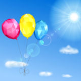 Sky, sun and low polygonal balloons. Background with sky, sun, clouds and low polygonal balloons made of triangular faces Royalty Free Stock Photography
