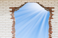 Sky with sunlight through the hole in the brick wall Stock Images