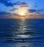 Sky Sunrise Sunset Sun Ocean. A sunrise that could also be a sunset over the ocean with waves, clouds and pelicans royalty free stock photos