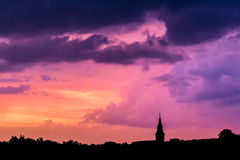 Sky after the sunset. Burning purple sky after the sunset with silhouette of a church and trees Stock Photo