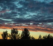 The sky at sunset is dotted with clouds. The clouds were present in the sky and the colors were beautiful. Drummondville, Quebec, Canada; July 18, 2016 Stock Images
