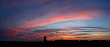 Sky at sunset with windmill. Panorama of the sky with red clouds at sunset with windmill Royalty Free Stock Photography