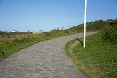 Sky and track 5. Photo of a stone track with green grass and sunlight Stock Photos