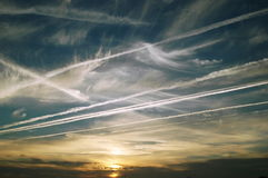 Sky Trails. Blue sky at sunset with lots of plane trails crossing Stock Photos