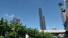 Sky train through green park and tall building under blue sky  in Bangkok center area Stock Images