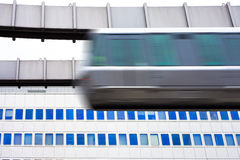 Sky-Train passing fast in front of office building Stock Photos