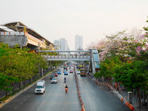 Sky train station, traffic and tabebuia rosea trees along the ro Stock Images