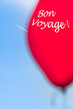Sky Travel Scene - Bon Voyage. Airplane contrail and part of a blurred red balloon with a textual message (copy space) at the blue sky Stock Photo