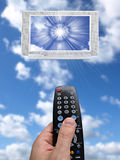 Sky tv. Hand holding a remote control aimed at a tv screen in the sky Stock Image