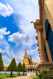 The sky vertically at the Emerald Buddha Temple. The yellow building is the Temple of the Emerald Buddha royalty free stock image