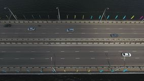 Sky view of wide bridge road with many riding cars on it over dark river. Sky view of big wide bridge road over dark river with plenty of moving cars on it in stock footage