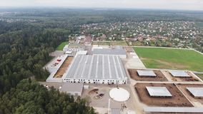 Sky view of modern clean fenced animal farm with corrals for cows and sheeps. Sky view demonstration of several roofs of buildings belonged to modern, clean stock video