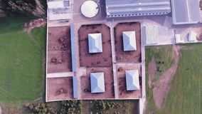 Sky view of roofs of modern fenced farm with large square animal corrals. Top view of grey roofs of buildings belonged to modern, clean, fenced animal farm with stock video footage