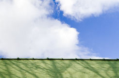 Sky with wall. Blue sky with clouds and green wall Royalty Free Stock Photography