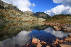 Sky in the water. A clear glacial lake in Retezat Mountains, Romania royalty free stock photos