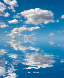 Sky on Water. Blue sky with fluffy clouds reflected on water surface Royalty Free Stock Image