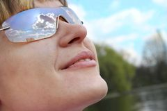 Sky in woman sunglasses. Young woman smiling, wearing sunglasses that reflect the sky stock photography