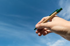 Sky writing. Hand with a pen writing in a blue sky Royalty Free Stock Photography