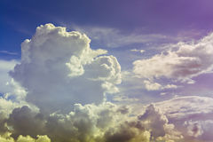 Sky. Yellow and purple on blue sky with fluffy low clouds Stock Photography