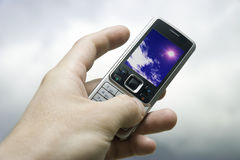 Sky in Your hand. Mobile phone in hand on blured cloudscape background. Blue sky on telephone screen Stock Image