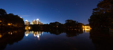 Skycrapper in Atlanta Downtown with reflection. A photo with group of buildings in Atlanta Downtown. The lake in piedmont park gives the beautiful night scene a Stock Photo