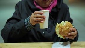 Skydd för hemlös Fattig kvinna som äter hamburgaren och dricker te sjuklig mat stock video