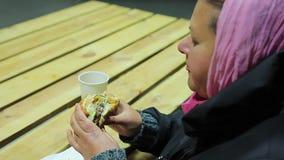 Skydd för hemlös Kvinna som äter hamburgaren och dricker te sjuklig mat lager videofilmer