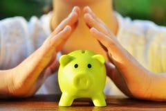 Skydda dina besparingar - med händer som täcker den gröna spargrisen royaltyfria bilder