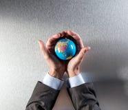 Skyddande affärsman som rymmer jorden inom händer för miljöomsorg Royaltyfri Foto