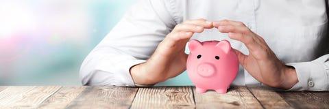 Skyddande händer över den rosa spargrisen - begrepp för finansiell säkerhet royaltyfri foto