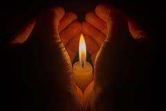 Skyddande händer runt om en brinnande stearinljus Arkivfoto