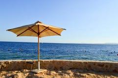 Skyddande härliga paraplyer som göras av gult tyg från torkade filialer mot den blåa himlen, på kusten av det salta havet på arkivbild