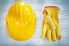 Skyddande handskar för byggnadshjälmläder på det vita brädet Arkivbilder