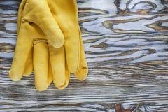 Skyddande handskar för gult läder på träbräde Royaltyfri Fotografi