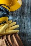 Skyddande handskar som bygger bältet för hjälmöronskyddhjälpmedel på träb arkivfoton