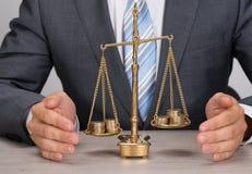 Skyddande rättvisaskala för affärsman med mynt arkivbild