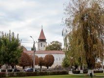 Skyddande väggar och watchtower med klockan av den stärkte kyrkliga Prejmeren i den Prejmer staden i Rumänien Arkivfoto