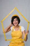 Skyddar bärande guling för kvinnabyggmästaren hjälmen och den total- innehavhusramen Royaltyfri Bild